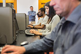 Teacher standing at front of computer class