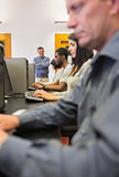 Teacher standing and smiling in computer class