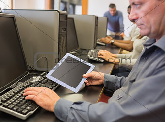 Man in computer class looking at tablet pc