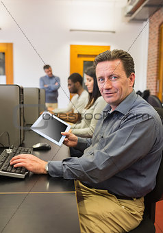 Mature student in computer class holding tablet pc