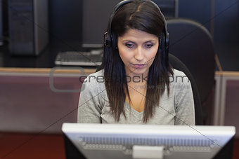 Black-haired woman concentrating on computer