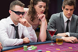 Men and woman sitting at poker table