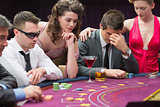 Man losing at poker table with woman comforting him