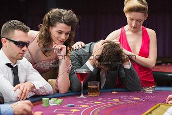 Woman comforting man losing at poker
