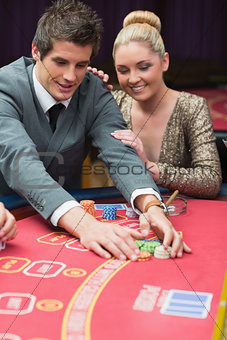 Man winning at poker with woman next to him