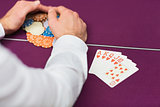 Man winning at poker with royal flush