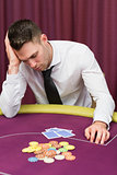 Man leaning on poker table looking disappointed