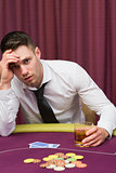 Man drinking whiskey at poker table