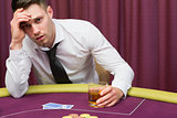 Man leaning on poker table drinking whiskey