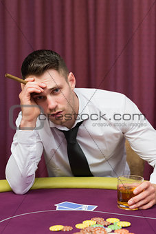 Worried man holding a cigar at poke at table