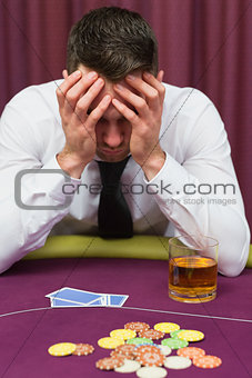 Man leaning on poker table looking worried