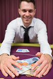 Man grabbing money at poker table