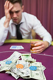 Man with whiskey glass leaning on poker table in casino