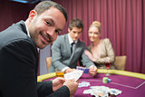 Man smiling and looking up from poker game
