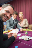 Man smiling while sitting at poker table