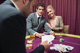 Couple playing poker and smiling