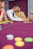 Happy people placing bets at poker game