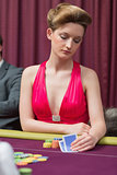 Woman sitting at table holding cards