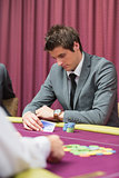 Man looking at his cards in poker game