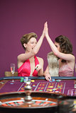 Women high fiving at roulette table