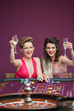 Women raising champagne glasses at roulette table