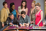 Men playing roulette as women are watching