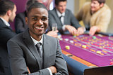 Smiling man sitting arms crossed at roulette table