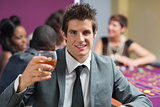 Man raising whiskey glass at roulette table