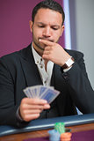 Man looking at his cards thinking