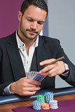 Man holding a cigar looking at his cards