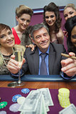 Women surrounding man at roulette table