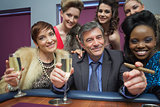 Happy man surrounded by women at roulette table