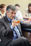 Man with cigar raising whiskey glass at roulette table