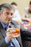 Man lifting glass of whiskey at roulette table