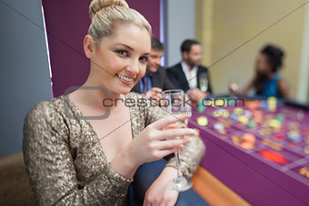 Blonde lifting champagne glass at roulette table