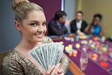 Blonde woman holding fan of dollars