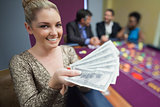 Woman holding out fan of dollars