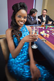 Woman at roulette table holding champagne glass