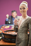 Woman smiling with champagne glass at roulette wheel