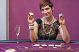 Woman at poker game holding up chips