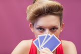 Woman in a casino holding cards up to face
