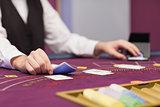 Dealer distributing cards at table