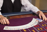 Dealer dealing out cards at roulette table