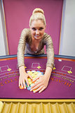 Smiling woman grabbing chips in a casino