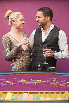 Couple drinking champagne at poker table