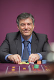 Smiling man playing roulette in a casino