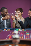 Three people celebrating in a casino with champagne