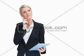 Blonde looking thoughtful while holding a tablet