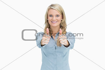 Blonde woman cheerfully doing thumbs up