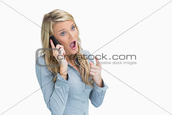 Woman looking shocked on the phone